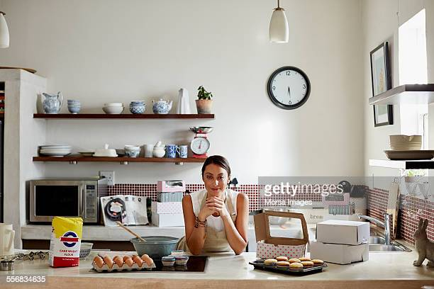 Confident woman preparing cupcakes in kitchen