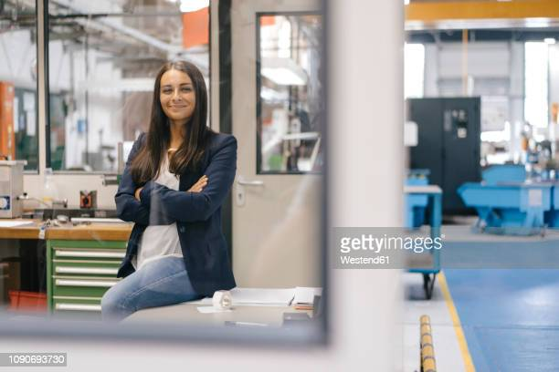 Confident woman sitting in high tech enterprise, standing in factory workshop with arms crossed