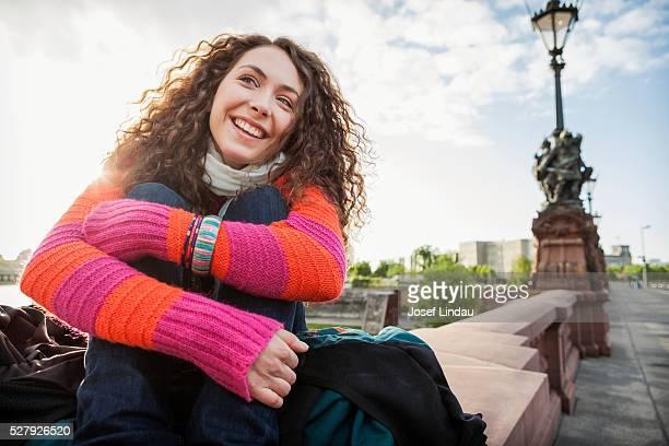 Confident woman sitting on a bridge