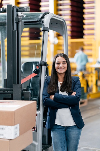 Confident woman standing in logistics center, with arms crossed - gettyimageskorea
