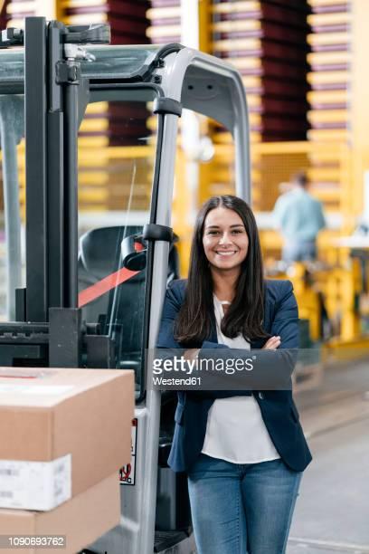 confident woman standing in logistics center, with arms crossed - handel treiben stock-fotos und bilder