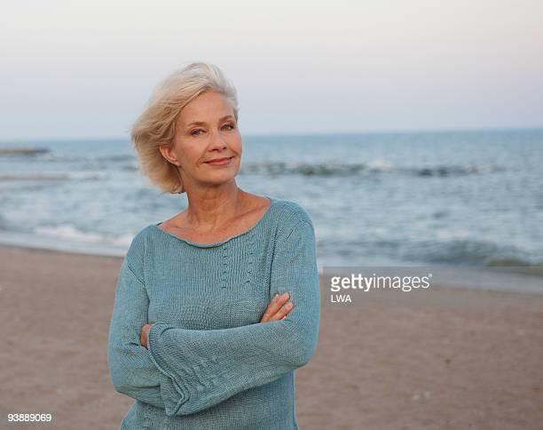 confident woman standing on beach - blond frauen strand stock-fotos und bilder