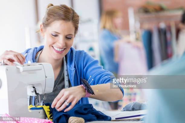 Confident woman uses a sewing machine