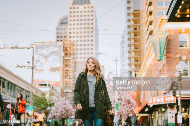a confident woman walks around downtown seattle - seattle stock pictures, royalty-free photos & images