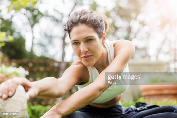 Confident woman warming up before jogging in park