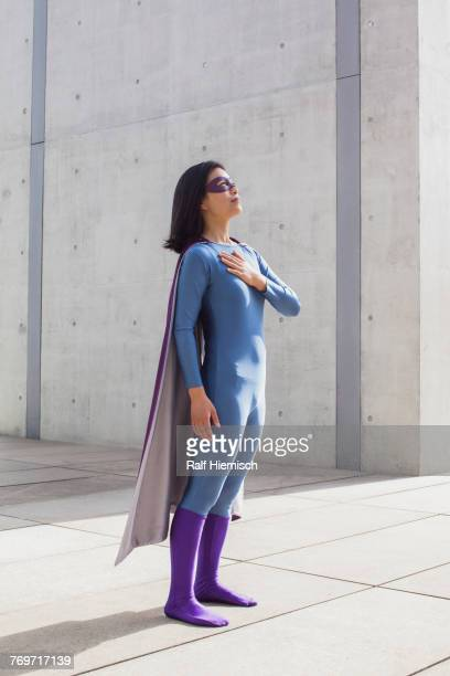 confident woman wearing superhero costume standing on floor by wall - cape garment stock pictures, royalty-free photos & images