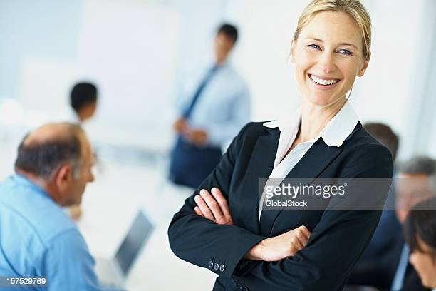 Confident woman with business people at the back