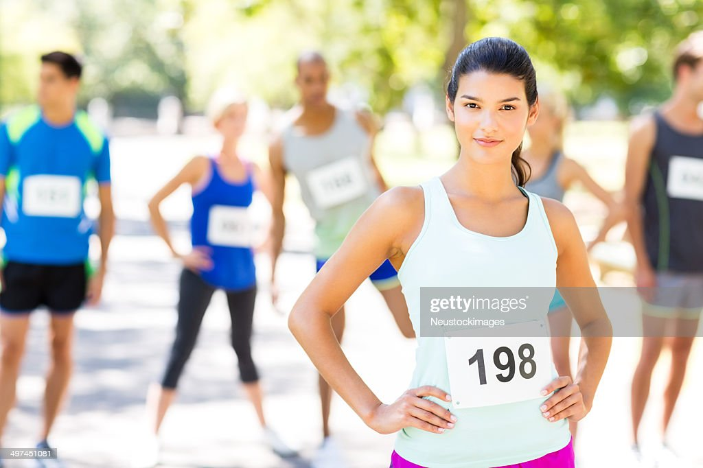 Confident Woman With Competitors In Background Before Marathon : Stock Photo