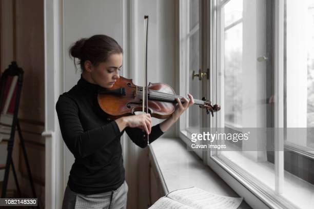 confident woman with sheet music on window sill playing violin in mansion - classical music stock pictures, royalty-free photos & images
