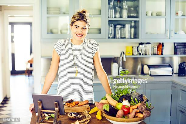 Confident woman with vegetables and digital tablet in kitchen