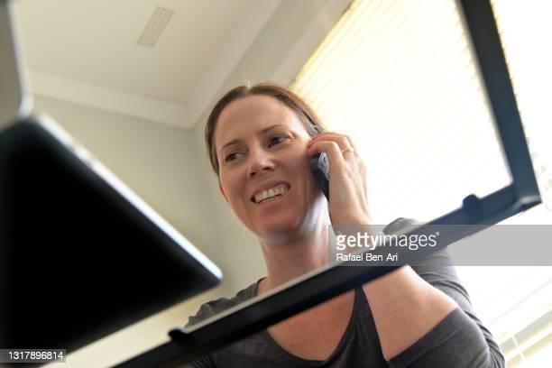 confident woman working from home on a laptop while having an online dating conversation on a cell phone - rafael ben ari bildbanksfoton och bilder