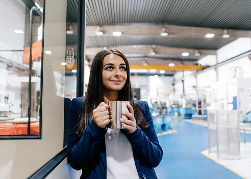 Confident woman working in high tech enterprise, drinking coffee - gettyimageskorea