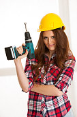 Confident woman works with batery drill machine DIY