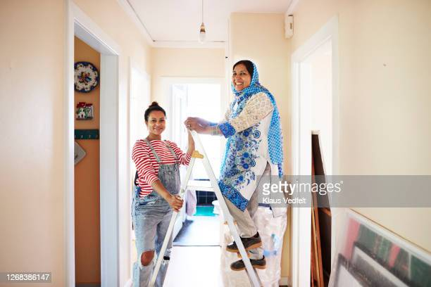 confident women renovating home together - genderblend stock pictures, royalty-free photos & images