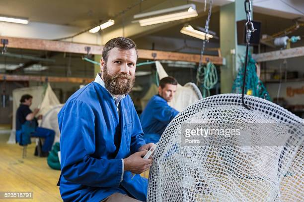 Confident worker preparing net at fishing industry