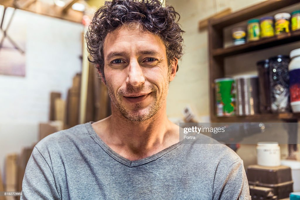 Confident worker smiling in workshop : Stock Photo