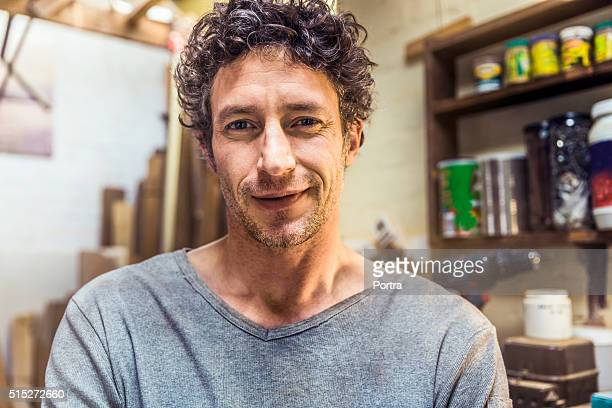 confident worker smiling in workshop - 30 39 years stock pictures, royalty-free photos & images