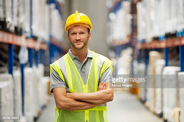confident worker standing in warehouse - schutzhelm stock-fotos und bilder