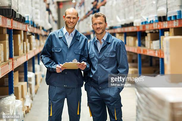 confident workers standing in warehouse - coveralls stock pictures, royalty-free photos & images