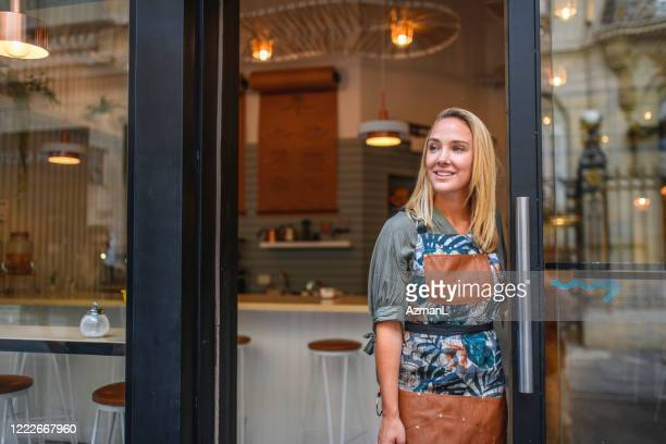 confident young argentine cafe owner standing at front door - independence stock pictures, royalty-free photos & images