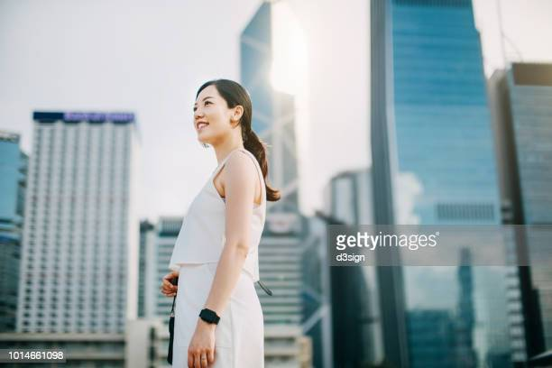 confident young asian businesswoman looking up to sky while standing against urban scene in financial district of hong kong - 見上げる ストックフォトと画像