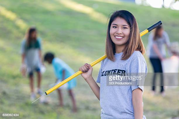 Confident young Asian female volunteer helps cleanup community park