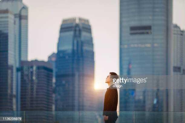 confident young asian man looking forward to start his day on a fresh bright morning against hong kong cityscape - calculating stock pictures, royalty-free photos & images