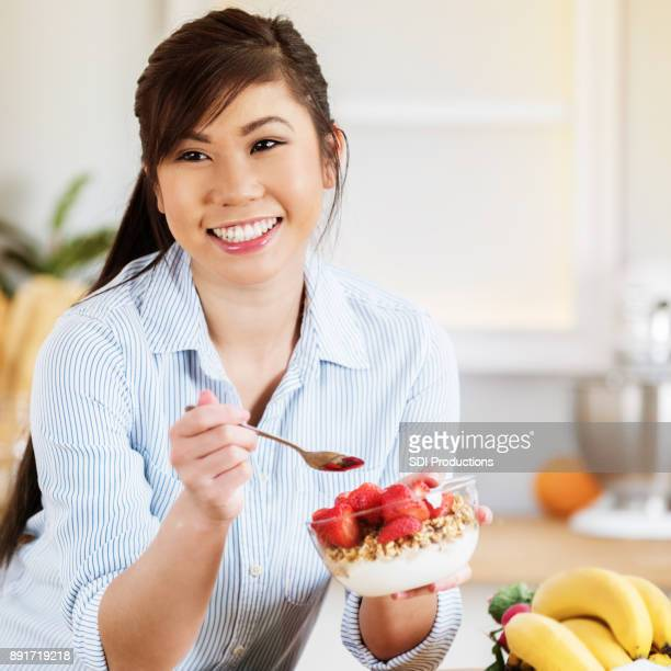 Confident young Asian woman enjoys a healthy breakfast