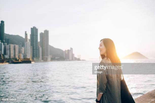 Confident young Asian woman looking out to the sea in the city on a fresh morning
