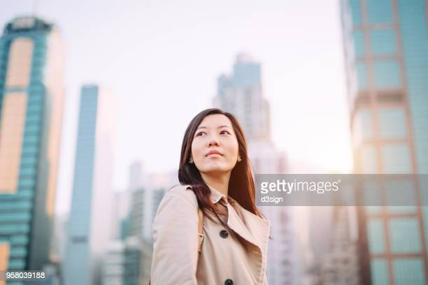 confident young asian woman looking up to sky with smile on a fresh bright morning against city skyline - antecipação - fotografias e filmes do acervo