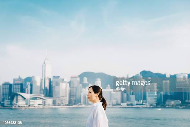 Confident young Asian woman standing against Hong Kong city skyline and looking the way forward