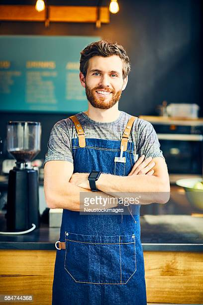 Confident young barista smiling in cafe