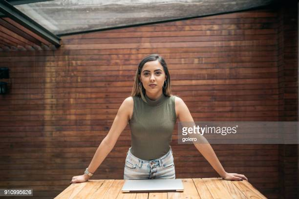 confident young brazilian businesswoman leaning on desk