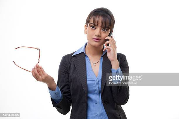 Confident young business woman holding glasses while using cell phone on white background