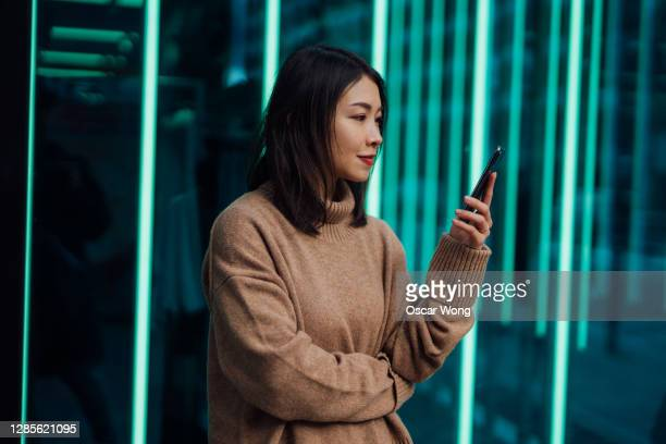 confident young business woman using smartphone against illuminated light tubes - illuminated stock pictures, royalty-free photos & images