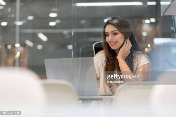 confident young business woman working on her laptop reading something while smiling - hispanolistic stock photos and pictures