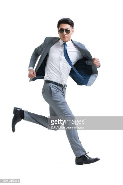 Confident young businessman running