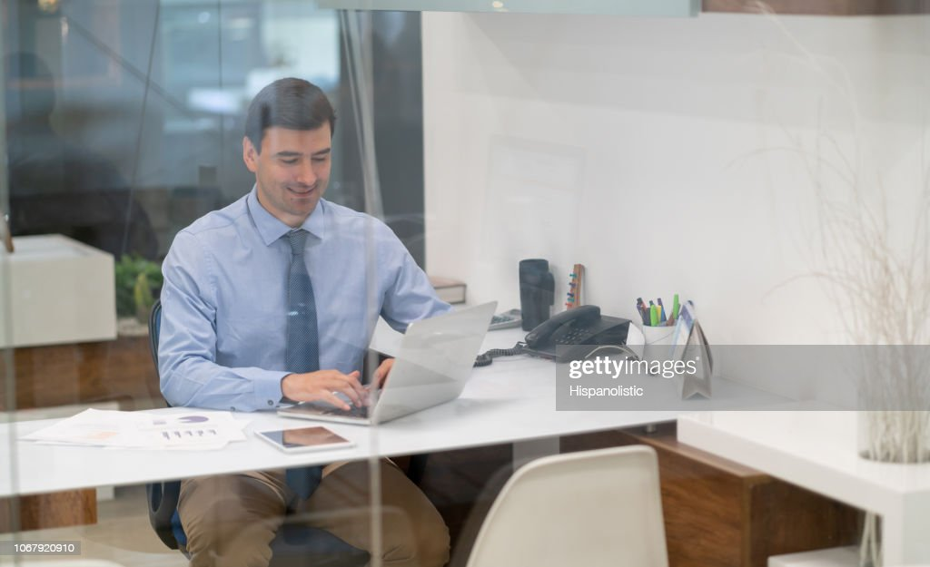 Confident young businessman sitting at the office working on laptop while smiling very happy : Stock Photo