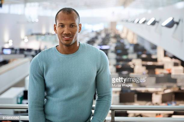 Confident young businessman standing at railing