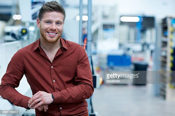 Confident young businessman standing in factory