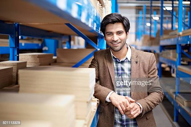 Confident young businessman standing in warehouse