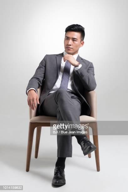 confident young businessman thinking - sentado fotografías e imágenes de stock
