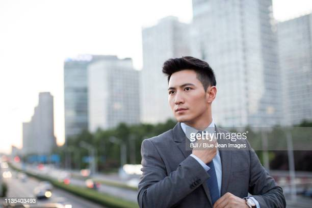 confident young businessman tying a tie - 東アジア ストックフォトと画像