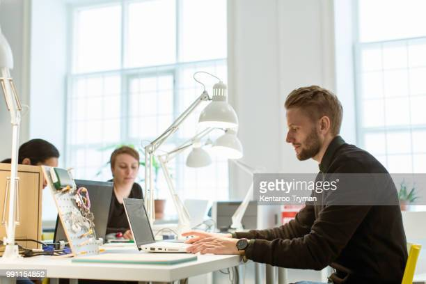 Confident young businessman using laptop while sitting at desk in creative office