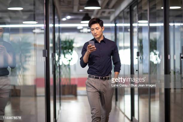 confident young businessman using smart phone - hands in pockets stock pictures, royalty-free photos & images