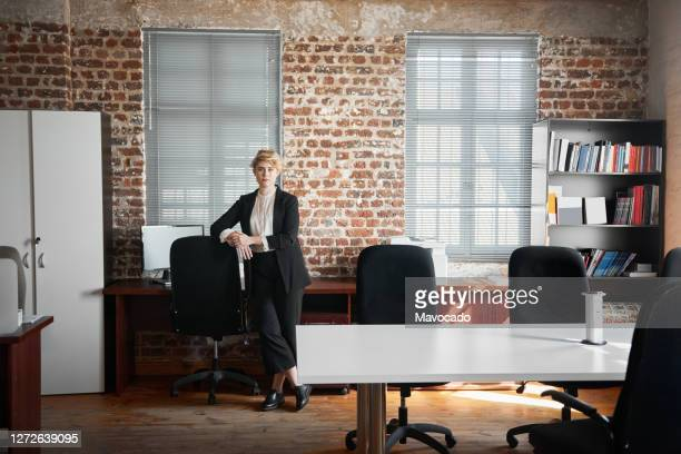 confident young businesswoman leaning on her office chair - 女性建築家 ストックフォトと画像