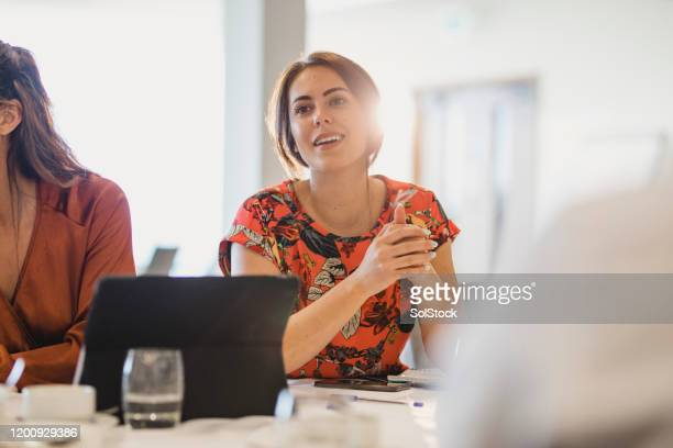 confident young businesswoman listening carefully at conference table - gender identity stock pictures, royalty-free photos & images