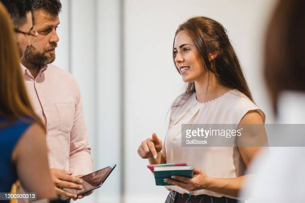 confident young businesswoman networking with colleagues - wedding planner foto e immagini stock