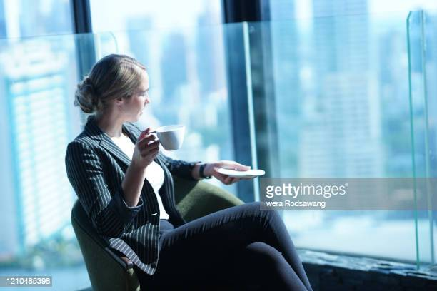 confident young businesswoman sit relaxing with coffee drink - 女性管理職 ストックフォトと画像
