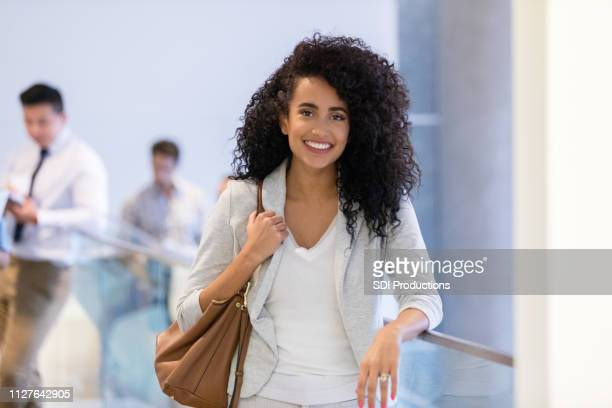 confident young businesswoman smiles for camera - shoulder bag stock pictures, royalty-free photos & images